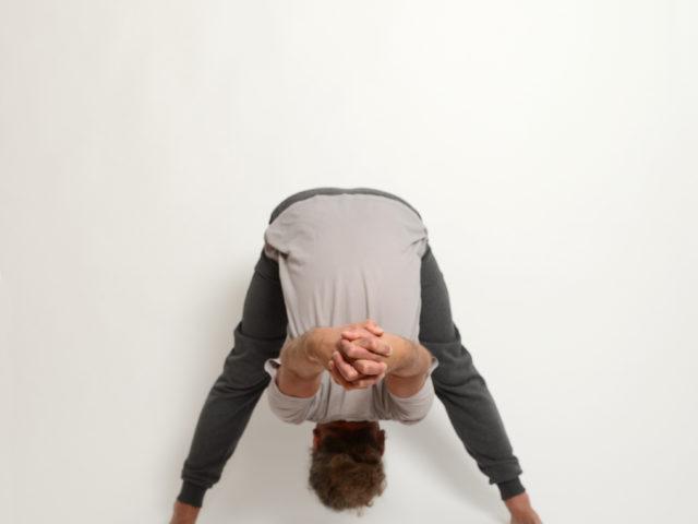 07 gegrätschte-stehende-Vorbeuge-Prasarita-Padottanasana-Yoga-im-Raum